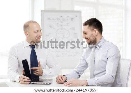 business, technology and office concept - two smiling businessmen with laptop having presentation in office - stock photo