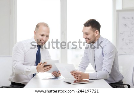 business, technology and office concept - two smiling businessmen with tablet pc computers and files in office - stock photo