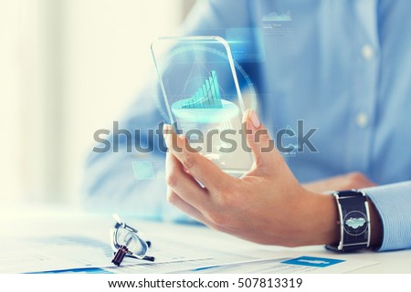 business, technology and people concept - close up of woman hand holding transparent smartphone with chart on screen at office