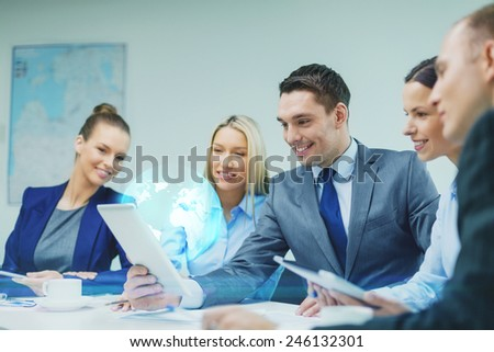 business, technology and people concept - smiling business team with tablet pc computer and virtual globe projection having discussion in office - stock photo