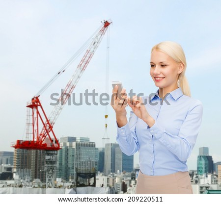 business, technology, building and people concept - smiling young businesswoman with smartphone over city building background - stock photo