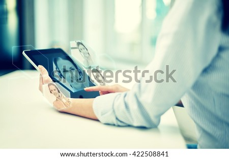 business, technology, communication and people concept - close up of woman holding tablet pc computer and having video chat with helpline operator at office or home - stock photo