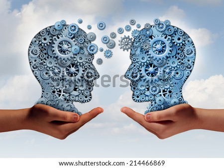 Business technology concept as two hands holding a group of  machine gears shaped as a human head as a symbol and metaphor for the transfer of industry information or corporate training. - stock photo