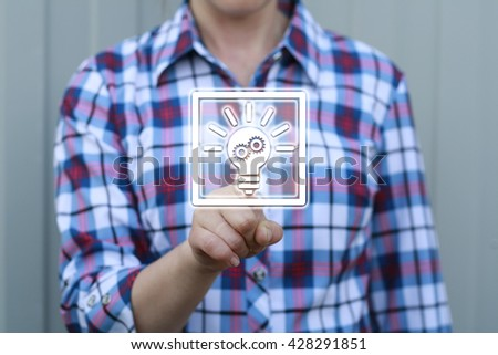 Business, technology concept - businesswoman pressing button with bulb on virtual screens. Ideas in business. Cyber idea. Innovation in business. Lightbulb, flask, idea, enlightenment, gear. - stock photo