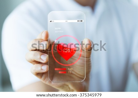 business, technology, health care and people concept - close up of male hand holding and showing transparent smartphone with heart rate icon - stock photo