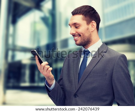 business, technology, internet and education concept - friendly young smiling businessman with smartphone - stock photo