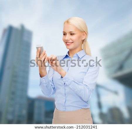 business, technology, internet and education concept - smiling young businesswoman with smartphone over business centre background - stock photo