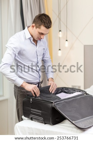 business, technology, internet and hotel concept - happy businessman packing things in suitcase in hotel room - stock photo