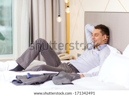 business, technology, internet and hotel concept - happy businesswoman lying in bed in hotel room - stock photo