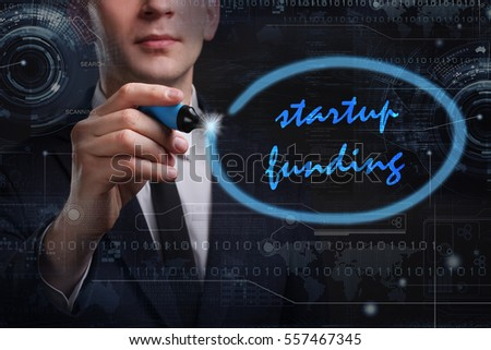 Business, Technology, Internet and network concept. Young business man writing word: startup funding