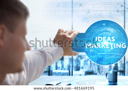 Business, Technology, Internet and network concept. Young businessman looks on a tablet, smart phone of the future. He sees the inscription: ideas marketing