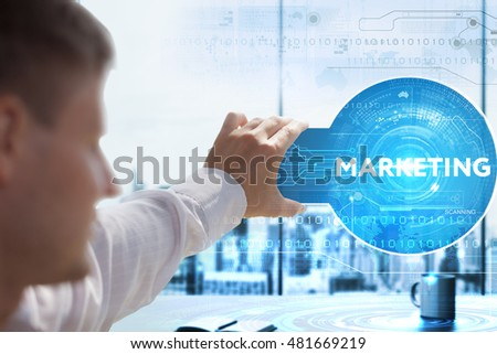 Business, Technology, Internet and network concept. Young businessman looks on a tablet, smart phone of the future. He sees the inscription: marketing