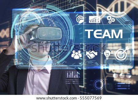 Business, Technology, Internet and network concept. Young businessman working in virtual reality glasses sees the inscription: team