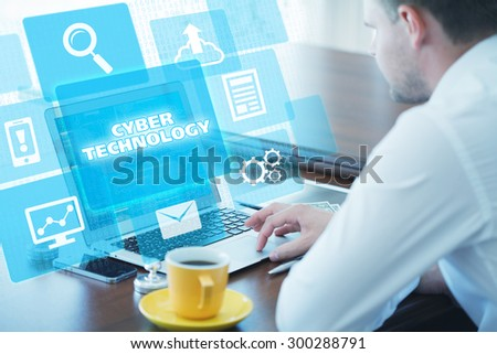Business, technology, internet and networking concept. Young businessman working on his laptop in the office, select the icon cyber technology on the virtual display - stock photo