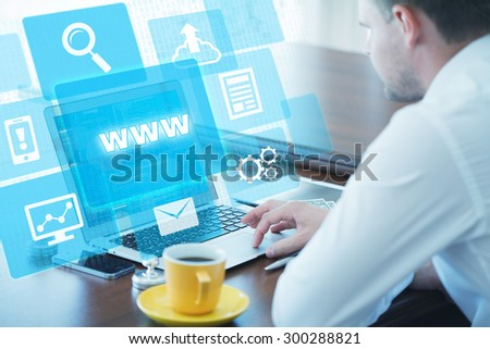 Business, technology, internet and networking concept. Young businessman working on his laptop in the office, select the icon www on the virtual display - stock photo