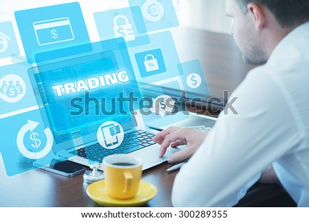 Business, technology, internet and networking concept. Young businessman working on his laptop in the office, select the icon trading on the virtual display. - stock photo