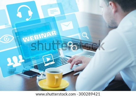 Business, technology, internet and networking concept. Young businessman working on his laptop in the office, select the icon webinar on the virtual display. - stock photo