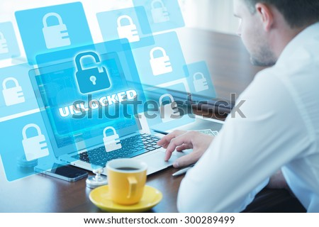 Business, technology, internet and networking concept. Young businessman working on his laptop in the office, select the icon unlocked on the virtual display. - stock photo