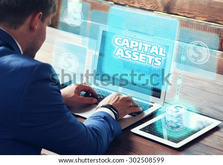 Business, technology, internet and networking concept. Young businessman working on his laptop in the office, select the icon capital assets on the virtual display. - stock photo