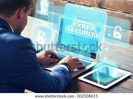 Business, technology, internet and networking concept. Young businessman working on his laptop in the office, select the icon cyber security on the virtual display. - stock photo