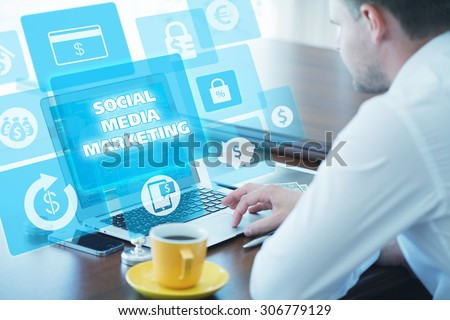 Business, technology, internet and networking concept. Young businessman working on his laptop in the office, select the icon SMM - Social Media Marketing on the virtual display. - stock photo
