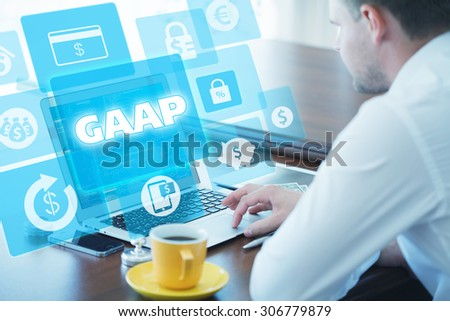 Business, technology, internet and networking concept. Young businessman working on his laptop in the office, select the icon GAAP â?? Generally Accepted Accounting Principles on the virtual display. - stock photo