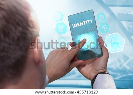 Business, technology, internet and networking concept. Young businessman working on his smartphone in the office, select the icon identity on the virtual display. - stock photo