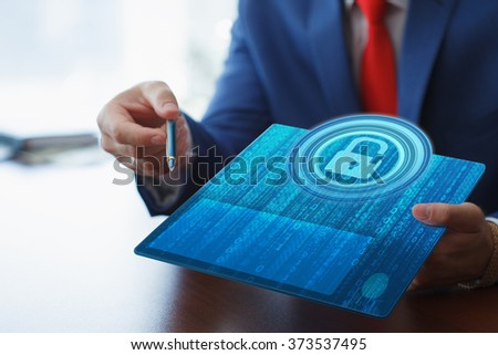 Business, technology, internet and networking concept. Young businessman working on his tablet in the office, select the icon security on the virtual display. - stock photo