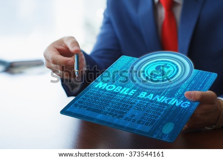 Business, technology, internet and networking concept. Young businessman working on his tablet in the office, select the icon mobile banking on the virtual display. - stock photo