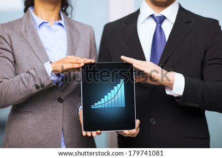business, technology, internet and office concept - businessman and businesswoman with graph on tablet pc screen in office