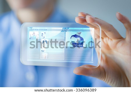 business, technology, internet and people concept - close up of woman hand holding and showing transparent smartphone with web site page on screen - stock photo