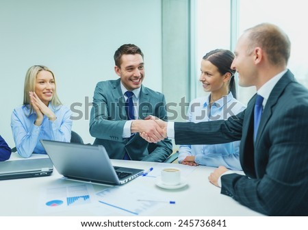 business, technology, partnership and people concept - two smiling businessman shaking hands in office - stock photo
