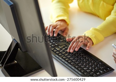 business, technology, school, people and education concept - close up of african american businesswoman or student girl hands with computer sitting at table - stock photo