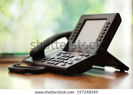 Business telephone with liquid crystal display on a desk in an office - stock photo