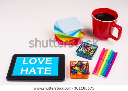 Business Term / Business Phrase on Tablet PC - Colorful Rainbow Colors, Cup, Notepad, Pens, Paper Clips, White surface - White Word(s) on a cyan background - Love Hate - stock photo