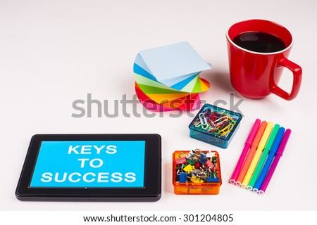 Business Term / Business Phrase on Tablet PC - Colorful Rainbow Colors, Cup, Notepad, Pens, Paper Clips, White surface - White Word(s) on a cyan background - Keys To Success - stock photo