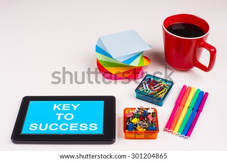Business Term / Business Phrase on Tablet PC - Colorful Rainbow Colors, Cup, Notepad, Pens, Paper Clips, White surface - White Word(s) on a cyan background - Key To Success - stock photo
