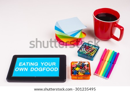 Business Term / Business Phrase on Tablet PC - Colorful Rainbow Colors, Cup, Notepad, Pens, Paper Clips, White surface - White Word(s) on a cyan background - Eating Your Own Dogfood - stock photo