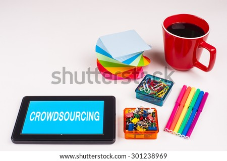 Business Term / Business Phrase on Tablet PC - Colorful Rainbow Colors, Cup, Notepad, Pens, Paper Clips, White surface - White Word(s) on a cyan background - Crowdsourcing - stock photo