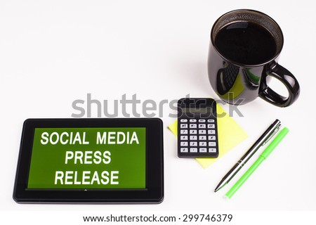 Business Term / Business Phrase on Tablet PC - Cup of coffee, Pens, Calculator and a green/yellow note pad on a White surface - White Word(s) on a green background - Social Media Press Release - stock photo