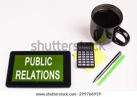 Business Term / Business Phrase on Tablet PC - Cup of coffee, Pens, Calculator and a green/yellow note pad on a White surface - White Word(s) on a green background - Public Relations - stock photo