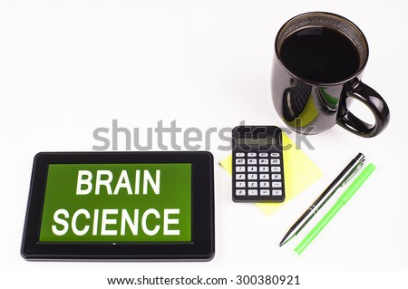 Business Term / Business Phrase on Tablet PC - Cup of coffee, Pens, Calculator and a green/yellow note pad on a White surface - White Word(s) on a green background - Brain Science - stock photo
