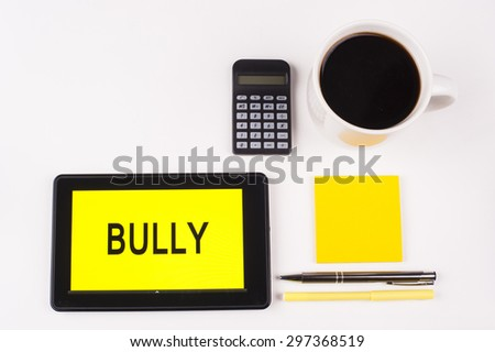 Business Term / Business Phrase on Tablet PC with a cup of coffee, Pens, Calculator, and yellow note pad on a White Background - Black Word(s) on a yellow background - Bully - stock photo