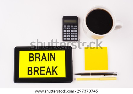 Business Term / Business Phrase on Tablet PC with a cup of coffee, Pens, Calculator, and yellow note pad on a White Background - Black Word(s) on a yellow background - Brain Break - stock photo