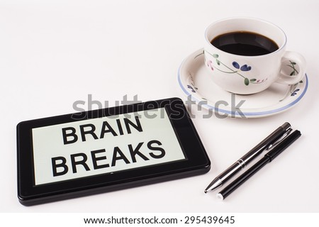 Business Term / Phrase on Tablet PC with a cup of coffee and pens on a White Background - Black Word(s) on a white background - Brain Breaks - stock photo