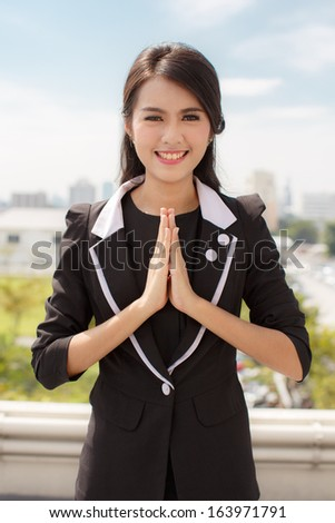 business thai women with typical welcome expression sawasdee,On the building in Bangkok - stock photo