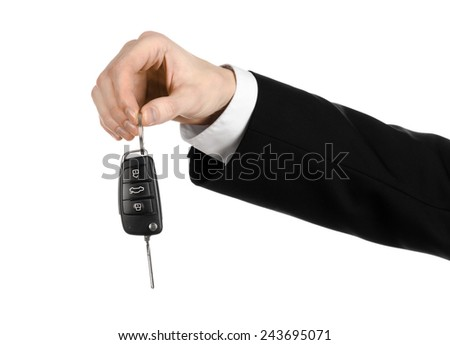Business theme: car salesman in a black suit holding a car key isolated on white background - stock photo