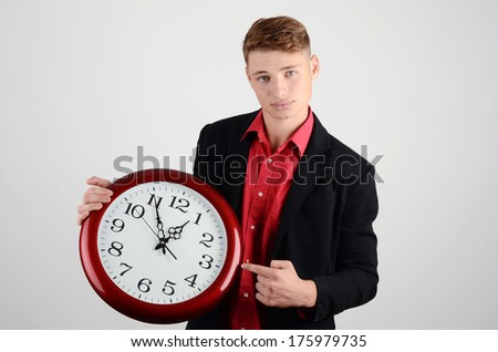 Business time. Business man holding and pointing to a big clock.