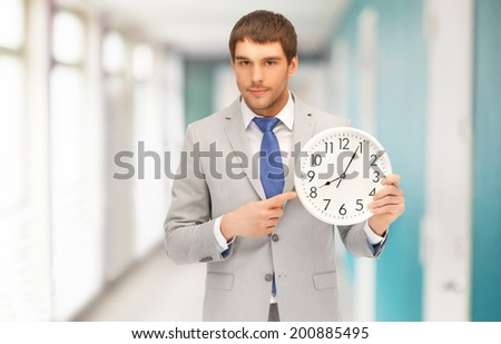business, time management and office concept - handsome businessman pointing finger to wall clock - stock photo