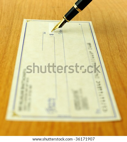 business transaction using a check, shallow focus on the pen tip - stock photo